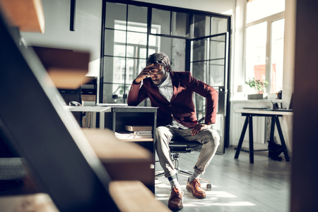 Too much work. African-American businessman feeling tired and overloaded with too much work