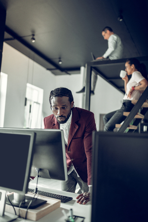 Looking at screen. Dark-skinned businessman looking at the screen of computer after receiving e-mail