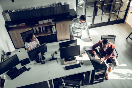 Businessmen working. Top view of successful prosperous businessmen working in the team in spacious office Banco de Imagens