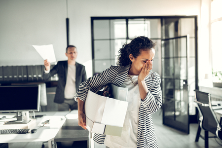 Secretary feeling emotional. Curly dark-haired secretary feeling emotional after being fired by her angry boss Banco de Imagens