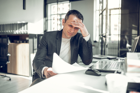 Too many complications. Businessman having too many complications while working on report in the office Imagens