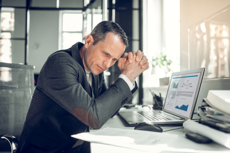 Working on report. Businessman wearing stylish jacket feeling busy while working on financial report