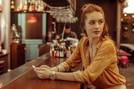 A girl at the bar. Beautiful alluring charming young-adult red-haired appealing girl holding a phone in hands and sitting at the bar counter Фото со стока