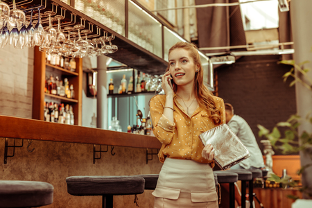 Young woman on the phone. Appealing focused surprised charming alluring young woman wearing brown blouse and skirt speaking on the phone while being at the bar