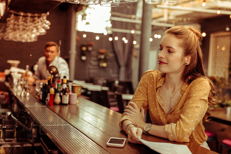 Sitting at the bar. Bewitching attractive charming adult nice-appealing lady with long red hair wearing a brown blouse sitting at the bar counter