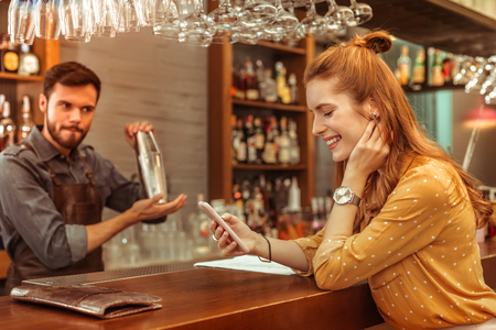 Looking at the phone. Happy smiling beaming long-haired bewitching alluring young woman looking at the phone in hands while a handsome attractive adult bearded bartender mixing drinks.