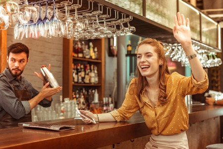 Waving woman. Cheerful joyous alluring charming beautiful red-haired laughing bar visitor emotionally waving to someone