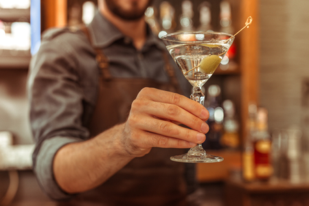 A martini cocktail. Close-up photo of an adult male bar worker holding a martini cocktail in a hand