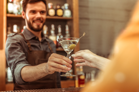 Handing a cocktail. Attractive smiling nice-looking dark-haired young-adult bar worker handing a martini cocktail to a female customer