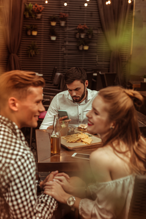 Flirting friends and lonely guy. Happy smiling cheerful good-looking young-adult radiant cheerful man and woman flirting with each other while their bearded friend is clicking on his phone.