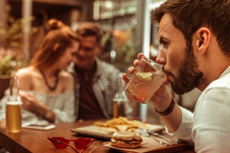 Feeling like the third wheel. Close-up face portrait of dark-haired bearded handsome young-adult man lonely sipping a cocktail while his mates hugging each other Imagens