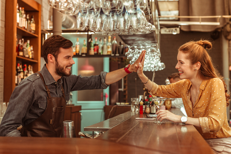 Giving a high five. Radiant beautiful delightful smiling glowing red-haired young-adult woman giving a high five to a dark-haired bearded nice-looking bar worker