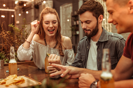 Having fun with friends. Charming long-haired nice-appealing young woman and two happy laughing attractive guys having fun and playing games at the bar Banco de Imagens