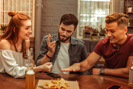 Playing games with friends. Three happy smiling cheerful nice-appealing young-adult attractive friends playing games at the bar while having drinks Banco de Imagens