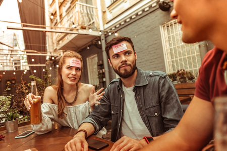Games at the bar. Confused attractive cheerful good-looking active vigorous mates spending time at the bar playing a hedbanz game Imagens