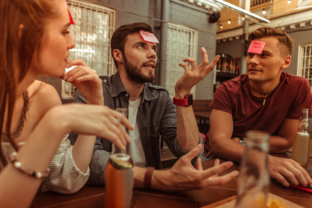 Playing games with friends. Attractive handsome dark-haired young-adult stylish man playing a hedbanz game along with his friends at the bar.