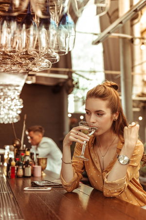 Drinking cocktail. Red-haired charming elegant bewitching radiant alluring young-adult female in stylish clothing enjoying drinking martini cocktail at the bar 스톡 콘텐츠