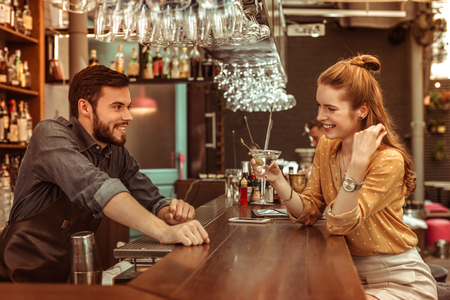 Talking to a bartender. Red-haired preprocessing radiant delightful young-adult beaming glowing woman talking to a smiling cheerful dark-haired bartender while holding a martini cocktail at the bar