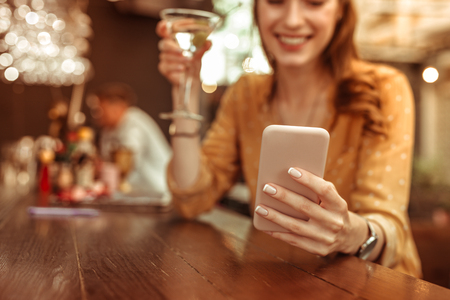 Holding a phone. Close-up photo of female hands holding a phone and clicking on it at the bar 스톡 콘텐츠
