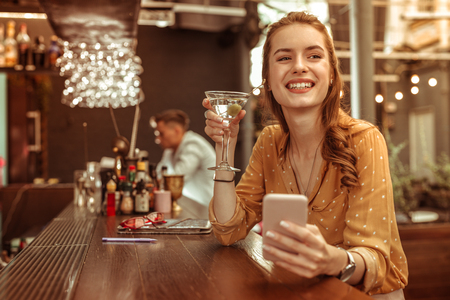 A woman with a martini. Happy smiling radiant beautiful charming stylish pretty young female with red hairdo holding a phone and a martini cocktail in hands