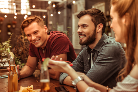 Smiling men. Smiling beaming attractive happy stylish young-adult two men sitting at the bar table