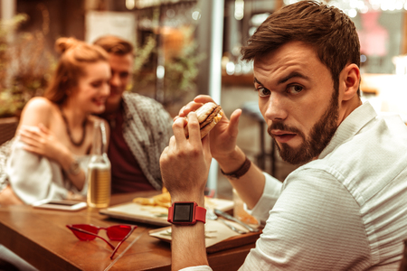Displeased man. Portrait of displeased dissatisfied attractive appealing handsome dark-haired bearded man with a burger in hands feeling jealous while his friends hugging.