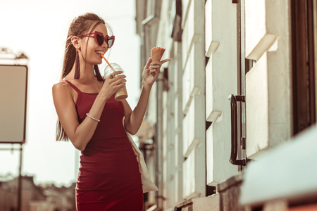 A woman with ice latte. Dark-haired pleasing alluring appealing bewitching lady wearing trendy eyeglasses and red dress drinking ice-latte while walking the streets Stock Photo