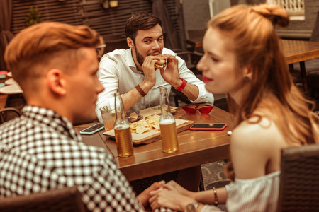 Looking enviously. Dark-haired displeased nice-looking attractive bearded adult man wearing blue shirt looking enviously at his holding hands mates while eating a burger at the bar