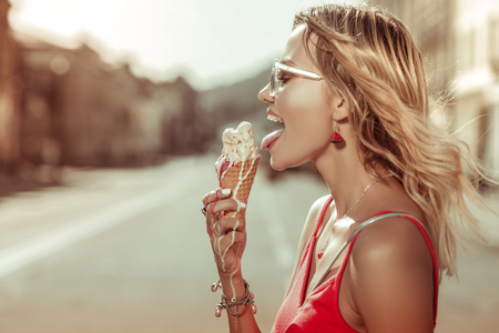 Melting ice-cream in hands. Profile portrait of fair-haired good-looking charming bewitching radiant beautiful woman wearing eyeglasses holding melting ice-cream in hands