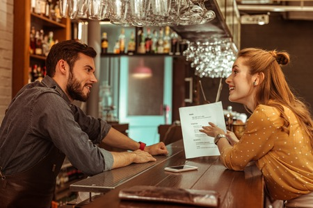 Discussing a menu. Bewitching red-haired delightful graceful joyful woman in a brown blouse discussing a menu with handsome attractive dark-haired bearded bartender.