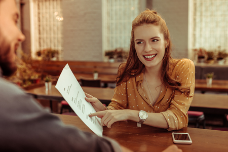 A woman with a menu. Beaming smiling glowing pretty red-haired stylish elegant girl pointing at the menu while sitting at the bar counter.
