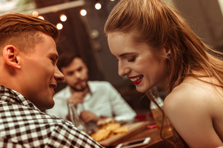 Flirting couple. Close-up face portrait of beautiful attractive young-adult cheerful joyful couple flirting with each other at the bar.