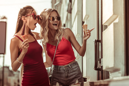 Women with ice-cream corners. Beautiful nice-appealing stunning charming arresting glamorous ladies wearing eyeglasses and holding ice-cream corners while doing window shopping Stock Photo