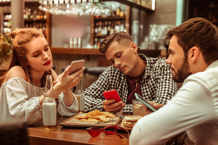 Being glued to the phones. Bored disinterested inattentive young-adult nice-appealing attractive group of three friends being glued to their phones while sitting at the bar