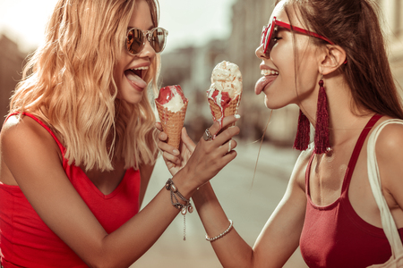 Women with ice-creams. Two beautiful alluring charming delightful young-adult sensuous beauties wearing red tops holding ice-creams in hands