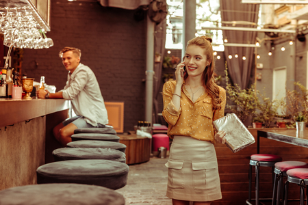 Talking on the phone. Delightful charming alluring slim red-haired cheerful young smiling lady having a phone conversation at the bar 스톡 콘텐츠