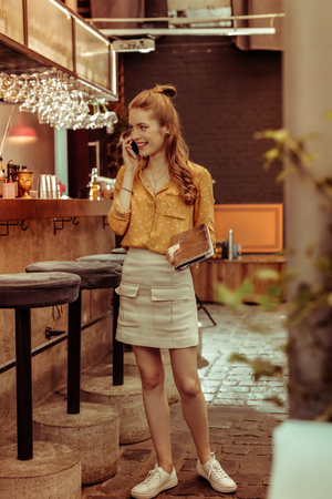 Speaking on the phone. Delightful nice-looking elegant slim cheerful young-adult smiling woman with red hair standing at the bar and talking on the phone