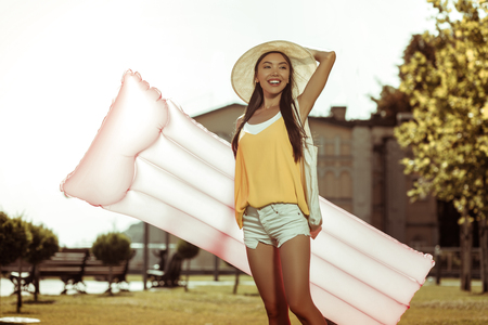 A woman with a mattress. Beautiful long-haired appealing smiling bewitching cheerful woman wearing hat and white short holding a pink inflatable air mattress