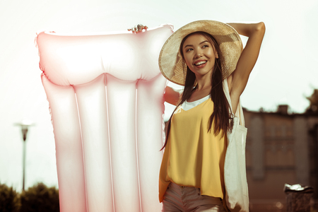 Holding a mattress. Radiant beaming dark-haired nice-appealing smiling bewitching cheerful woman wearing hat and white short holding a pink inflatable air mattress