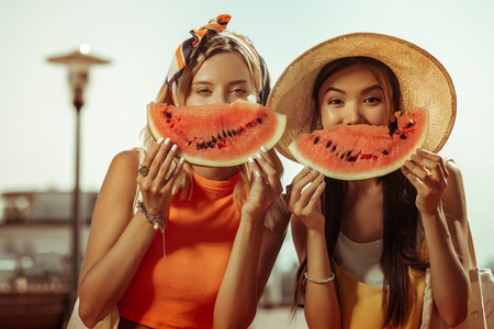 Portrait with the watermelon. Close-up portrait of contended alluring beautiful stylish girls posing with watermelon pieces in hands while being outdoors.