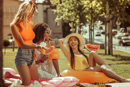 Sharing a laugh. Appealing bewitching beautiful lovely pretty nice-looking laughing smiling three women sharing a laugh during a picnic outdoors