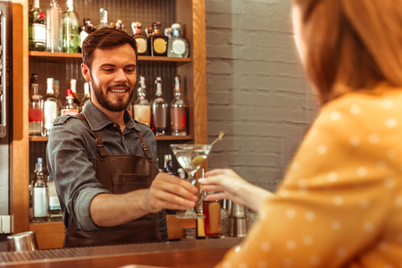 Giving a martini cocktail. Attractive beaming good-looking dark-haired adult bartender wearing dark apron giving a martini cocktail to a woman
