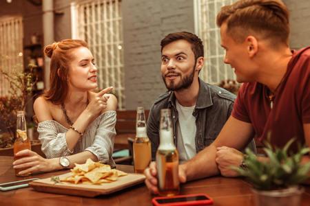 Beer with friends. Beautiful red-haired appealing young woman and two happy smiling attractive men sitting at the bar with beer Banco de Imagens