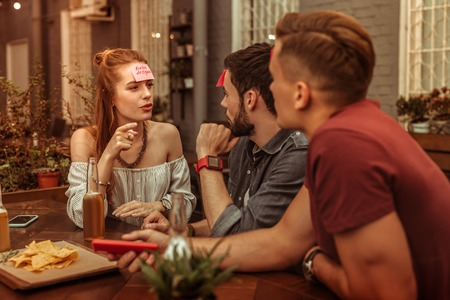 Woman playing hedbanz. Charming red -haired alluring bewitching young-adult woman wearing white top playing a hedbanz game with guys while being at the bar