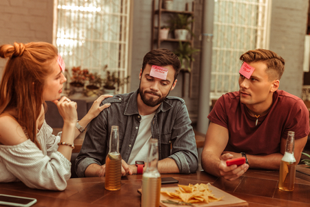 Playing hedbanz game together. Attractive joyous active good-looking vigorous young-adult radiant friends enjoying time at the bar while playing a hedbanz game together