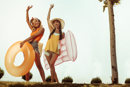 Girls with swimming stuff. Happy cheerful alluring good-looking nice-appealing bewitching joyful energetic young-adult girls wearing shorts and tops posing with swimming stuff outdoors