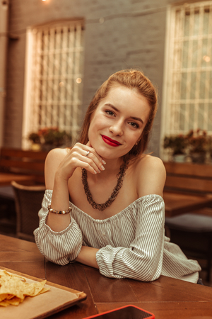 Beautiful red-haired woman. Face portrait of delightful radiant smiling beaming bewitching red-haired woman with open-shoulders white top sitting at the bar 스톡 콘텐츠 - 124984427