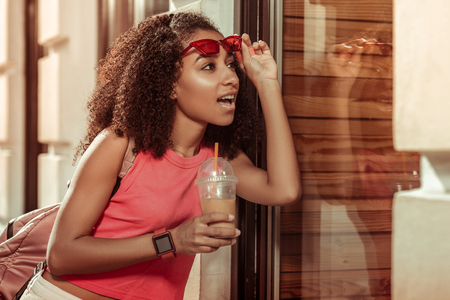 Surprised Afro-American woman. Bewitching appealing nice-looking charming Afro-American young-adult woman with curly hair looking surprisingly at the window and raising the trendy glasses off.