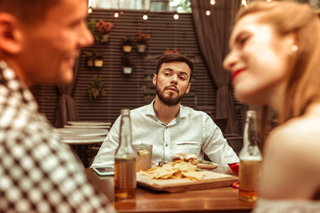 Jealous man. Jealous dark-haired bearded young-adult attractive nice-appealing gentleman wearing blue shirt looking at his flirting friends at the bar Imagens