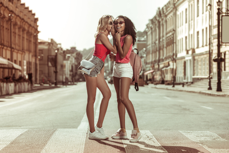 Whispering in ears. Alluring bewitching appealing charming slim blonde young girl whispering in ear of her dark-haired Afro-American charming friend in eyeglasses while crossing the road Stock Photo